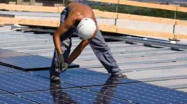Solar Panels Being Assembled in Array on Roof - iStockPhoto