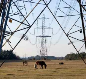 High voltage power transmission lines with pylons - iStockPhoto